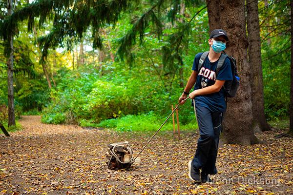 A Montessori student hauls wood on a service trip