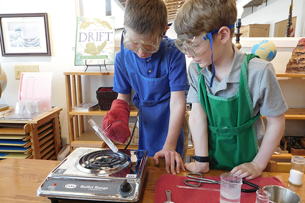 Two Montessori students explore their curiosity and conduct a science experiment